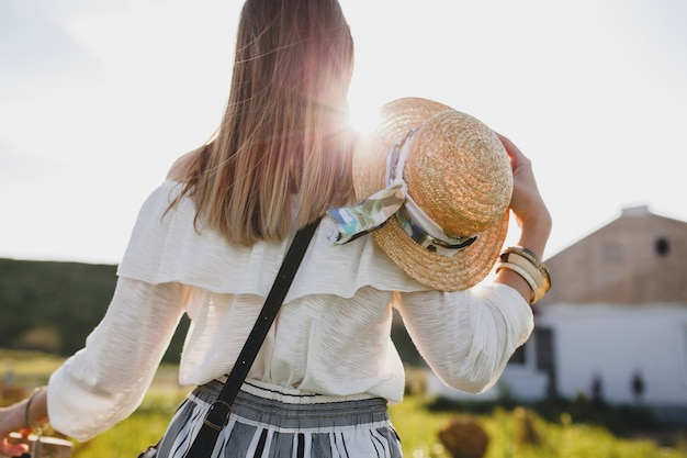 View from back on sunny beautiful stylish woman, spring summer fashion trend, boho style, straw hat, countryside weekend, long hair Free Photo
