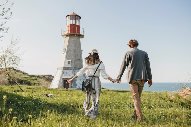 View from back on young couple hipster indie style in love walking in countryside, holding hands, lighthouse on background, warm summer day, sunny, bohemian outfit, hat Free Photo