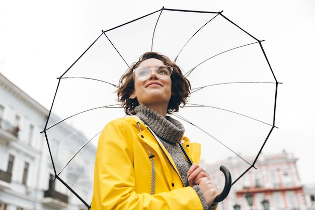 View from beneath of positive woman in yellow raincoat and glasses standing in street under big transparent umbrella during grey rainy day Free Photo