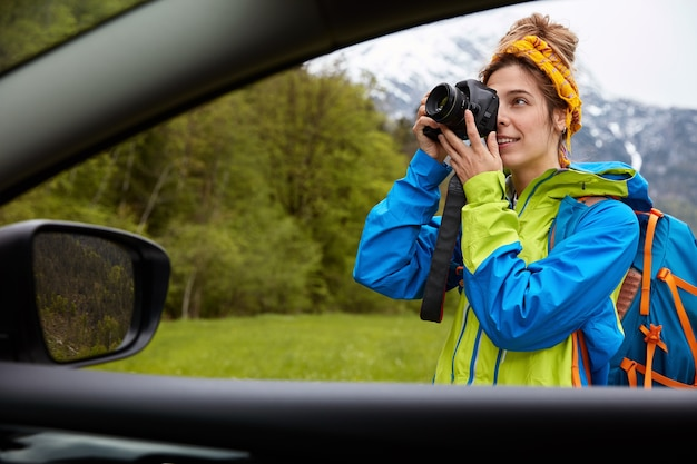전문 젊은 여성 사진 작가의 차에서보기 카메라에 사진을 찍고 산 풍경과 함께 그린 필드에 산책 무료 사진