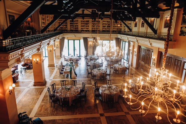 View from the ceiling of decorated celebration hall with round tables Free Photo