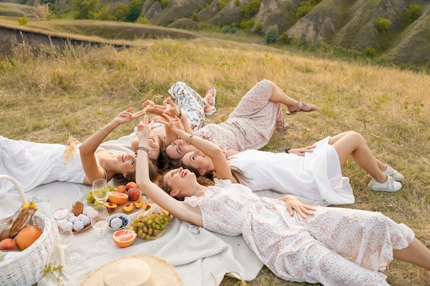View from above. the company of beautiful girlfriends have fun and enjoy a picnic outdoors Premium Photo
