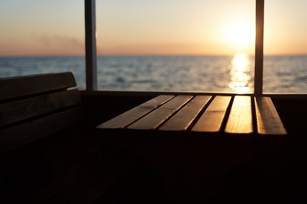 View from deck of beautiful sunset. unrecognazible person having promenade on cruise ship, admiring beautiful landscapes Free Photo