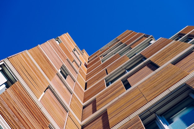 View from the floor of the facade of a modern building clad in ecological wood over clean blue sky Premium Photo