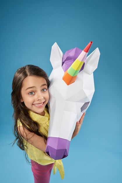 View from above of happy child keeping paper unicorn Free Photo