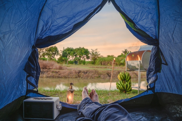 View from inside of tent with relaxing and campfire near swamp Premium Photo