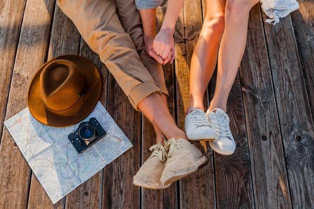 Vista dall'alto di gambe di coppia che viaggia in estate vestito con scarpe da ginnastica, moda stile hipster boho uomo e donna divertirsi insieme, mappa, cappello, macchina fotografica, visite turistiche, moda calzature Foto Gratuite
