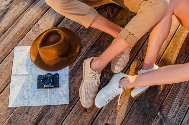 Vista dall'alto di gambe di coppia che viaggiano in estate vestite di scarpe da ginnastica Foto Gratuite