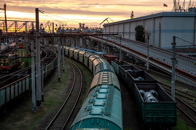 View from the railway bridge to freight trains at sunset. Free Photo