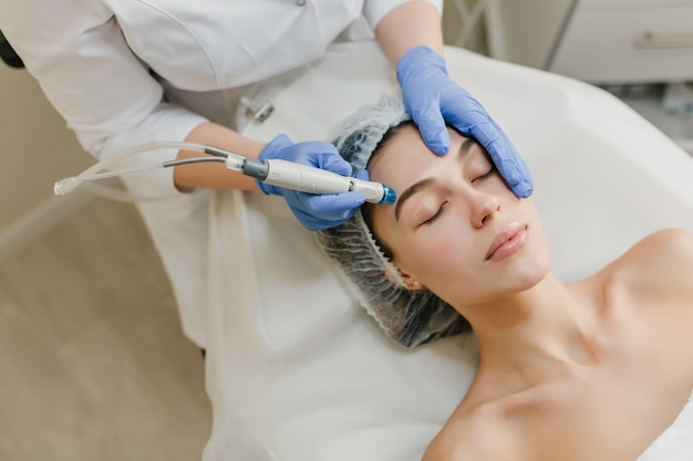 View from above rejuvenation of beautiful woman enjoying cosmetology procedures in beauty salon. dermatology, hands in blue glows, healthcare, therapy, botox Free Photo