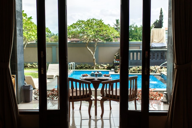 View from the room, balinese tropical breakfast of fruit, coffee and omelet for two people, Premium Photo