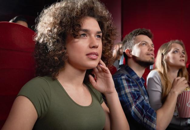 Вид со стороны возбужденной девушки, смотрящей интригующий фильм. Premium Фотографии