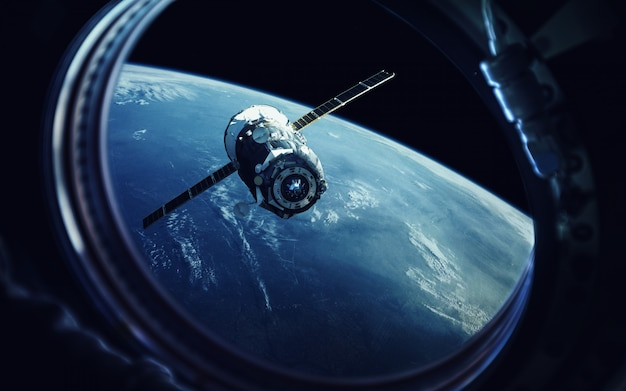 View from spaceship porthole. earth and spacecraft. Premium Photo