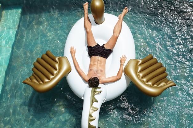 魅力的な筋肉ボディが大きなインフレータブルマットレスの上半身裸でリラックス、青い水でプールに浮かんでいる、昼寝、暑い日に日焼けをして若い白人男性の上からの眺め 無料写真