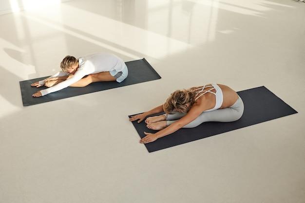 Vista dall'alto di due giovani uomo e donna con corpi muscolosi flessibili che indossano abiti sportivi che praticano yoga insieme, seduti su stuoie, facendo paschimottasana. sport, salute e flessibilità Foto Gratuite