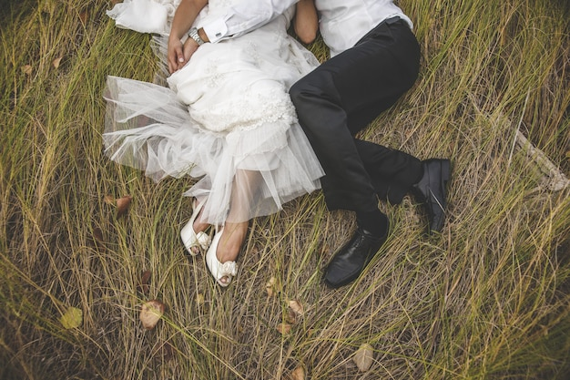 View from above of two newlyweds lying on the grass embracing each other. Premium Photo