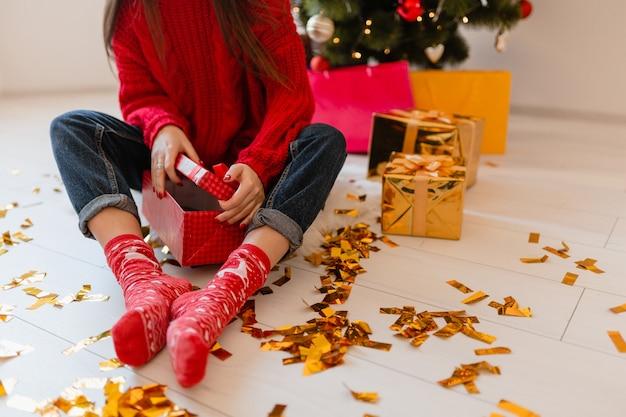 Vista dall'alto sulla donna in calzini rossi seduta a casa a natale su coriandoli dorati disimballaggio peresents e scatole regalo Foto Gratuite