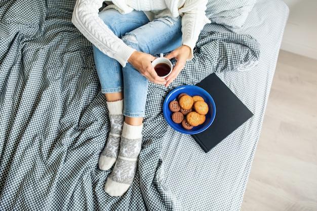 Vista dall'alto della donna seduta sul letto la mattina, bere il caffè in tazza, mangiare biscotti, colazione Foto Gratuite