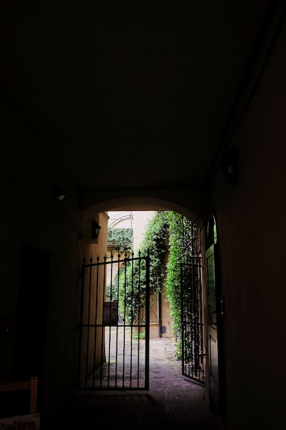 View of the gate in the courtyard through the dark arch tunnel Premium Photo