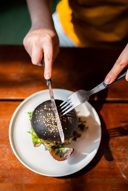 The above view of hands cuts broccoli quinoa charcoal burger topped with guacamole, mango salsa and fresh salad by knife and fork, served in a white plate. creative vegan meal for vegetarians. Premium Photo