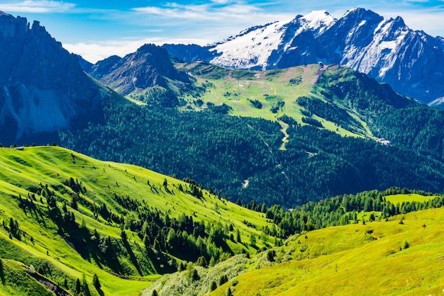 View of the italian alps mountain the dolomites with the snow the small village and the green hill in south tyrol, italy Premium Photo