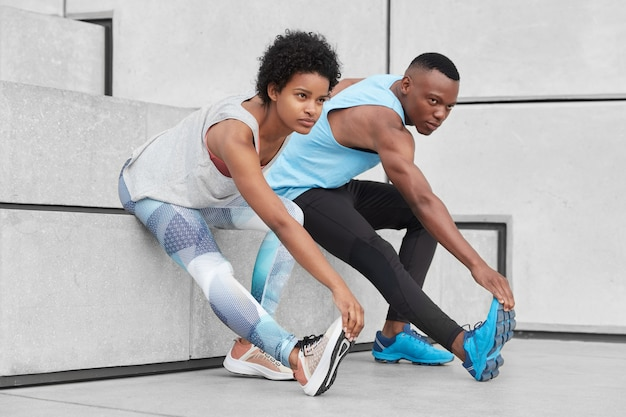 View of motivated teenagers demonstrate good flexibility, lean to feet, do stretching exercises near stairs, wear comfortable sneakers for training, have dark healthy skin, strong muscular body Free Photo