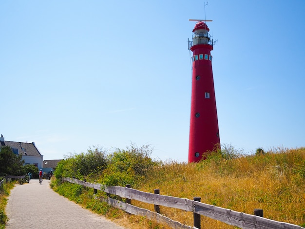 View of the north tower - lighthouse in schiermonnikoog islands one of the frisian islands, on sand dune against blue sky Premium Photo