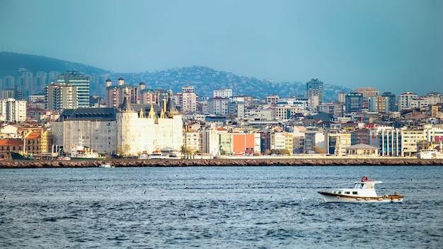 イスタンブール、ボスポラス海峡、前景に移動ボート、トルコの住宅と高度な近代的な建物のある地区のビュー 無料写真