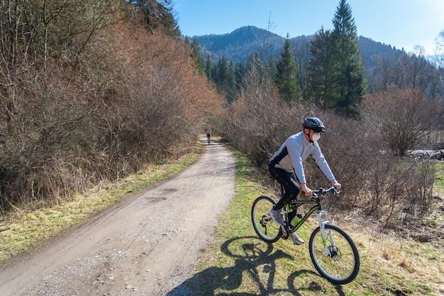 コロナウイルス検疫中に木々に囲まれた道路の自転車に乗っている男性の様子 無料写真