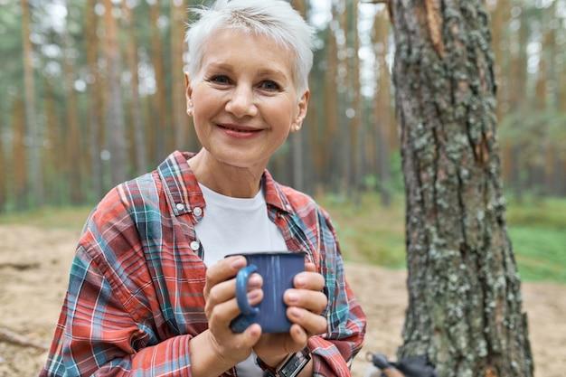 キャンプ場で屋外で休んでいるブロンドの髪を持つ愛らしい幸せなヨーロッパの女性年金受給者のビュー 無料写真