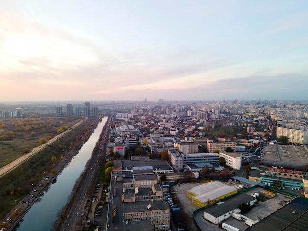 무인 항공기, 수로, 녹지와 호수가있는 공원, 여러 주거 및 상업용 건물, 일몰, 루마니아에서 부쿠레슈티의 전망 프리미엄 사진