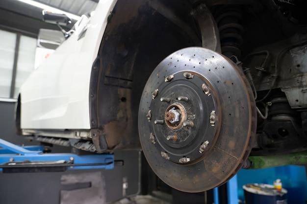Вид автомобиля дискового тормоза для замены шины в гараже Premium Фотографии