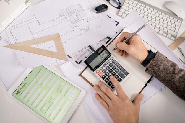 사무실에서 책상으로 작업하는 동안 펜과 계산기가 노트북에 메모를 작성하는 엔지니어의 손보기 프리미엄 사진