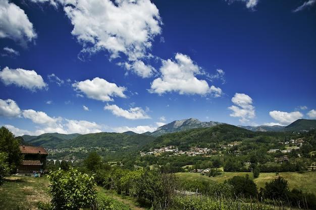 曇った青い空を背景に緑の丘の上の家のビュー 無料写真