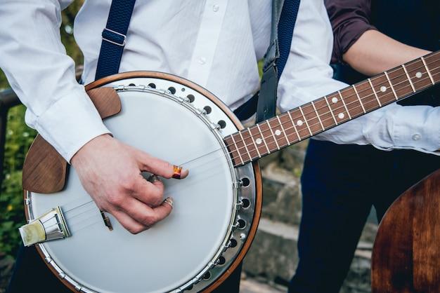 Вид музыканта, играющего на банджо на улице Premium Фотографии