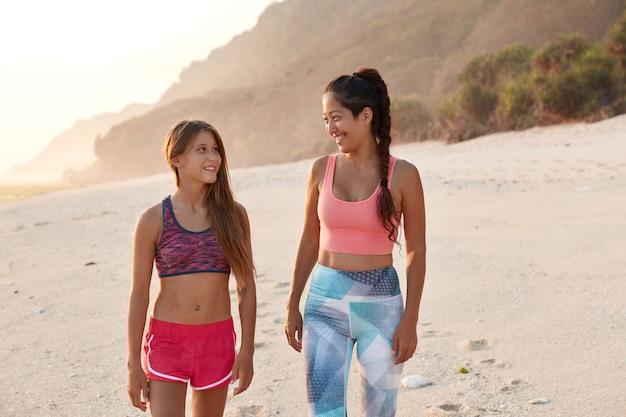 かなり若い同性愛者の女性の眺めはビーチを散歩している、友好的な話 無料写真