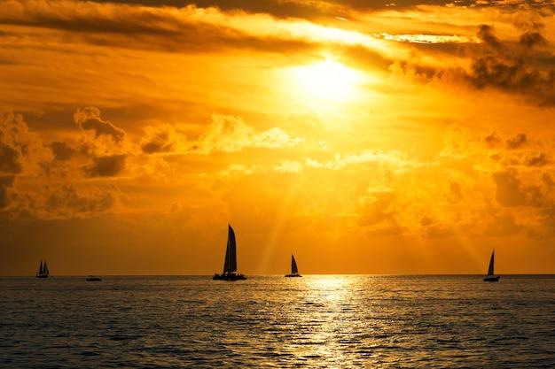 Вид на парусники в море на закате Premium Фотографии