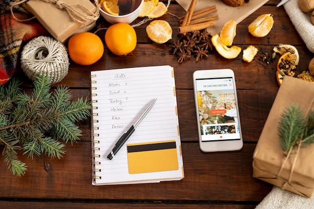 Вид на смартфон с промо, блокнот с ручкой, список и кредитную карту в окружении традиционных рождественских вещей на столе Premium Фотографии