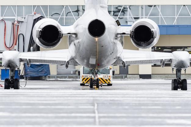 空港でプッシュバックしたときの航空機のエンジンとテールのビュー。 Premium写真
