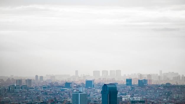 Вид на стамбул в пасмурную погоду, несколько высоких и низких зданий, туман, турция Бесплатные Фотографии