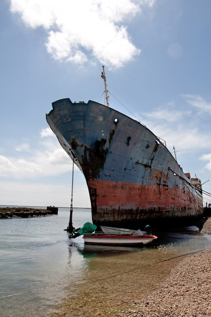 View of an old and rusty ship parked at the shoreline. Premium Photo