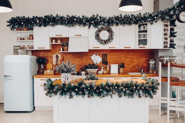 찬장과 부엌 보드 온통 크리스마스 장식과 함께 아름다운 흰색 부엌을 봅니다. 찬장에 크리스마스 화환이 있습니다. 소나무 콘과 함께 자연 전나무 나무 가지입니다. 프리미엄 사진