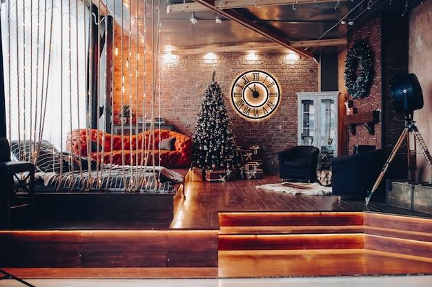 크리스마스 또는 새해 이리저리 현대적으로 장식 된 객실을 볼 수 있습니다. 로마 숫자, 빨간색 현대 소파, 바닥에 침대, 안락 의자 2 개 및 크리스마스 장식이있는 큰 시계. 로프트 디자인 인테리어. 프리미엄 사진