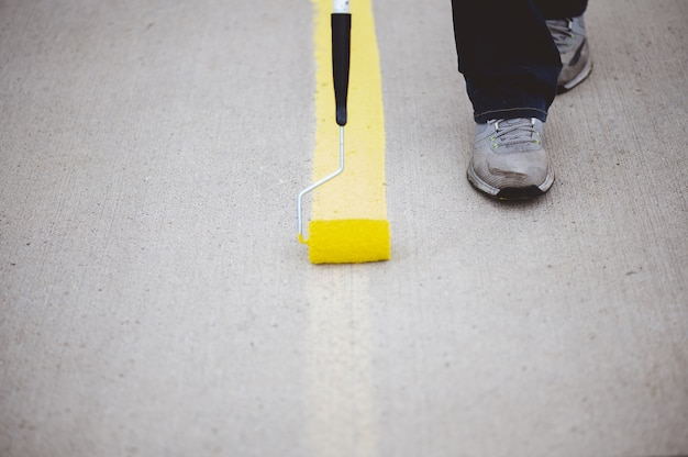 View of a person repainting the parking lines of the asphalt of a parking lot with yellow paint Free Photo