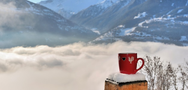 View on a red mug put on a snowy pole of a terrace above a sea of clouds in mountain Premium Photo