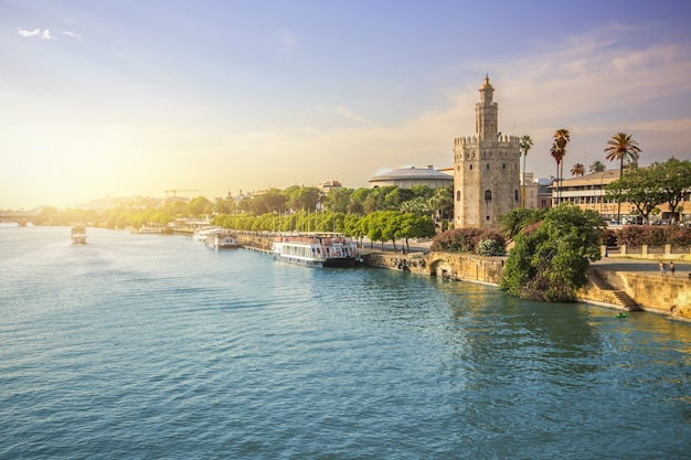 View of seville city and torre del oro during sunset with canoeing team in river Premium Photo