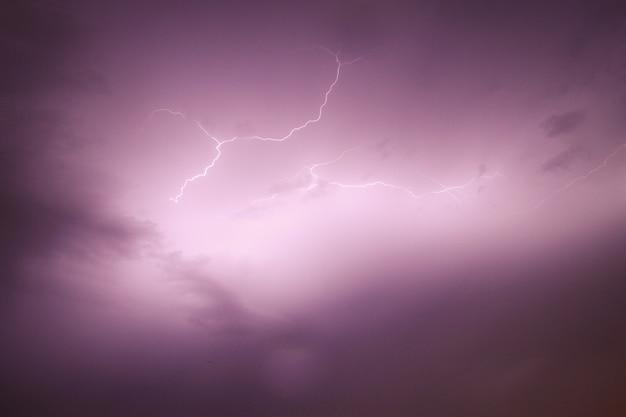Vista del cielo che cattura un fulmine con cieli nuvolosi viola Foto Gratuite