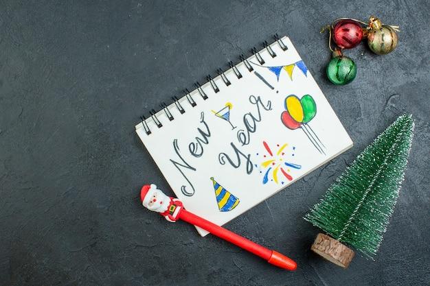 Sopra la vista del taccuino a spirale con la scrittura e la penna del nuovo anno accanto agli accessori della decorazione dell'albero di natale su fondo scuro Foto Gratuite