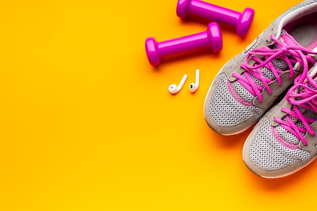 Above view sporty items on yellow background Free Photo