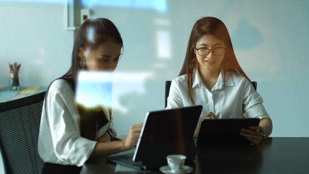 Вид через стеклянное окно на двух офисных работниц, консультирующихся по их проекту в конференц-зале Premium Фотографии